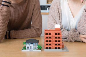 戸建てとマンションの模型を眺める夫婦