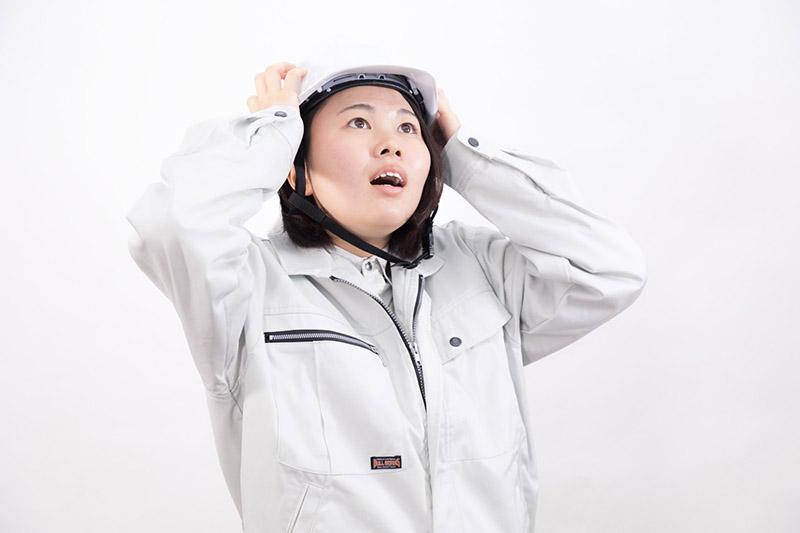 ヘルメットをかぶり頭を抱える女性