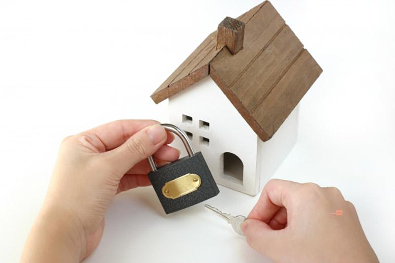 ミニチュアの家と南京錠(防犯イメージ)