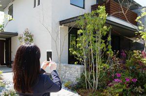 家の写真を撮る女性
